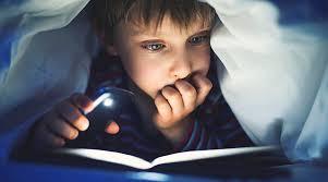 寝床で携帯電話を見る若者