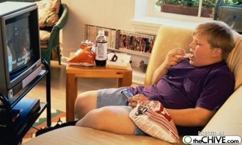 テレビを見ながらソファーに座り込んで 大きなポテトチップの袋を持ちバク食いしている太った人