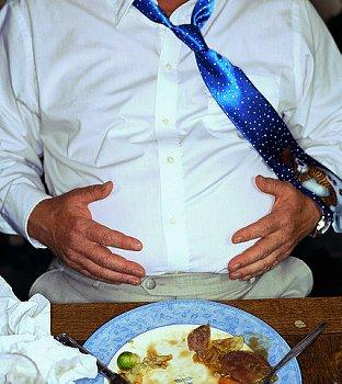 食後に突き出たお腹をさする人