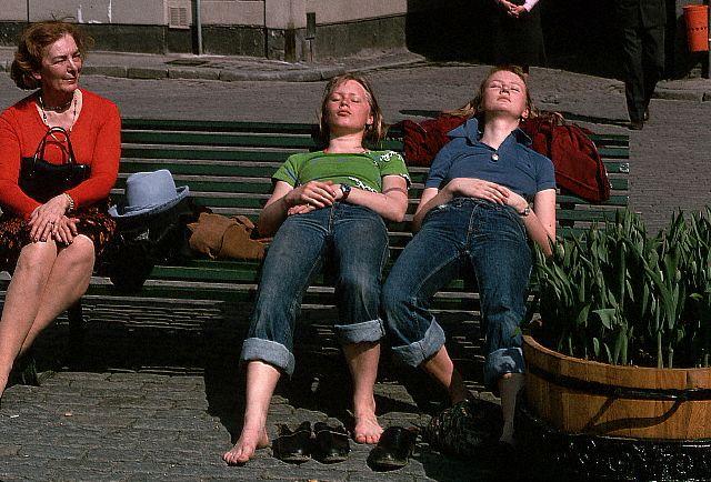 バス停で日光浴する若い女性