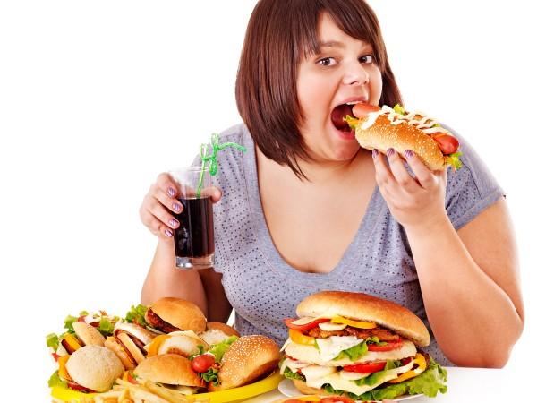 たくさんのファストフードをバク食いする太った女性