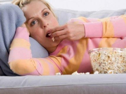 寝ながら大量のポップコーンをつまむ太った女性2
