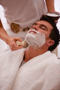 石鹸を塗って髭を剃る男性の写真