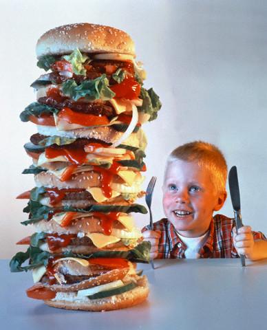 山盛りのハンバーガーを前にして嬉しそうな空腹な人