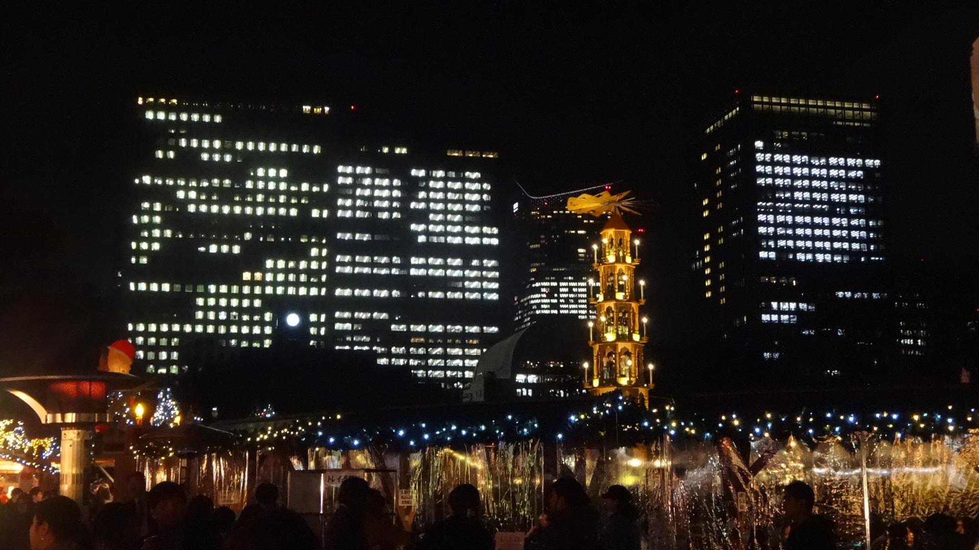 高層ビル群のライトアップをバックに立つクリスマスタワー