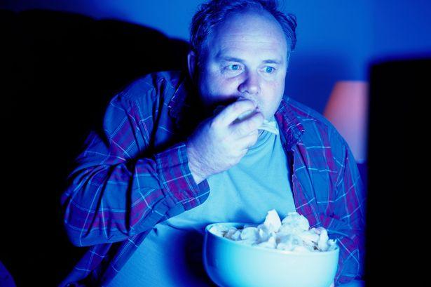 夜中にテレビを見ながら大きなポップコーンの箱を抱えてバク食いする男性