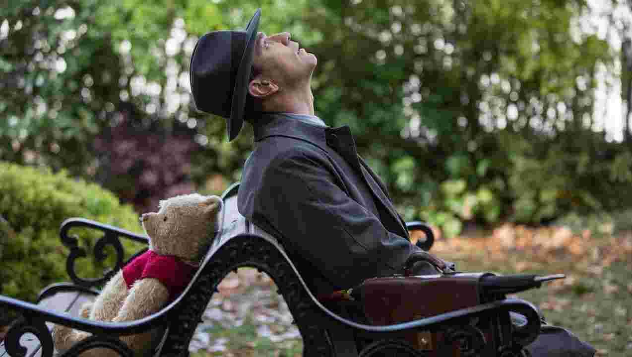 公園のベンチで再会した熊のプーさんとロビンの様子