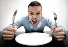 空の皿の前でお腹を減らしている人の写真