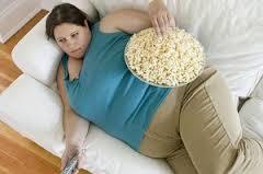 寝ながら大量のポップコーンをつまむ太った女性