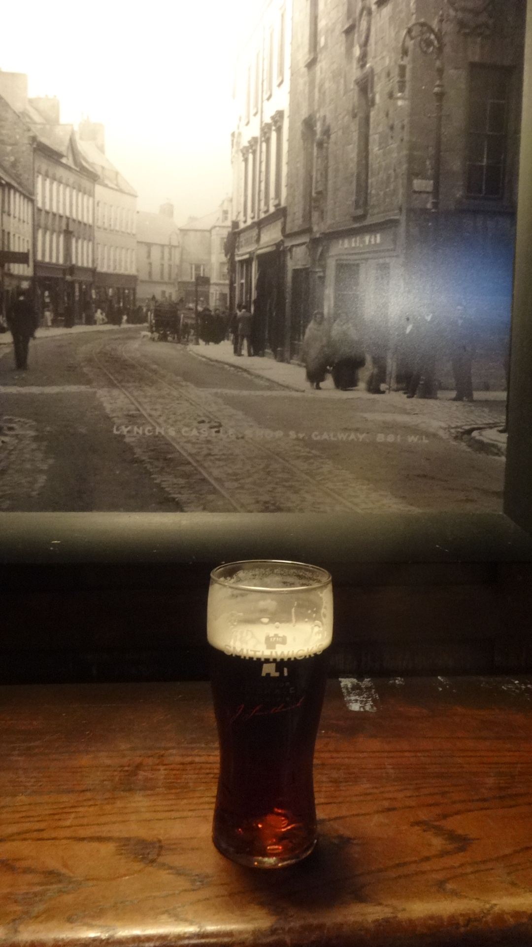 街の白黒の風景写真を背景にしたスミテイックスのグラス