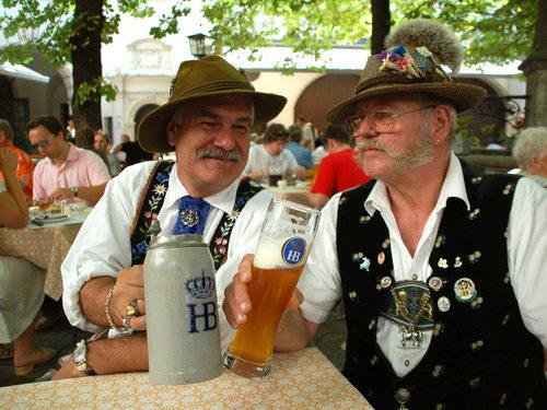 陶器のジョッキでビールを飲んでいる人の写真