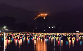 灯篭流しをしている川越しに見える送り火