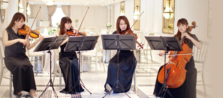 サロンで優雅に演奏する女性弦楽四重奏グループの写真