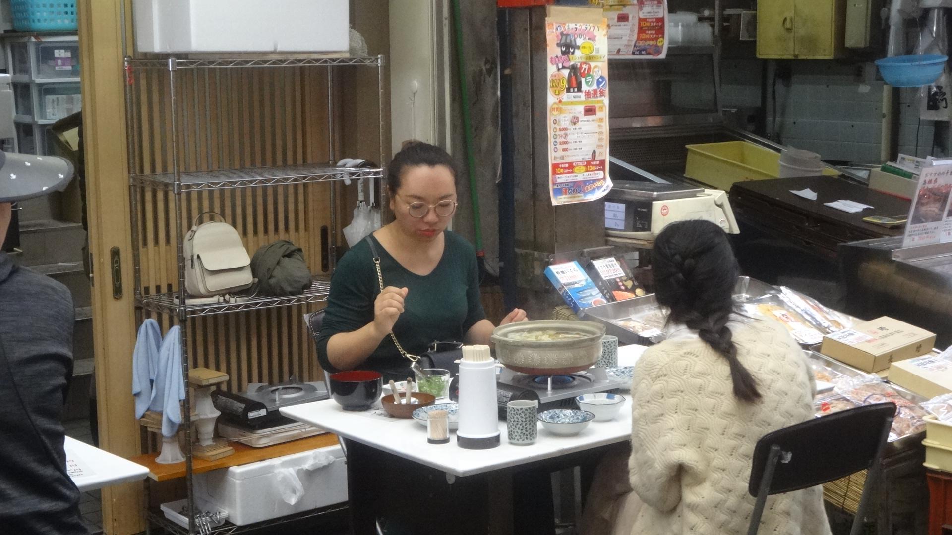 簡易テーブルでてっちり鍋を食べている人たち