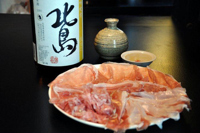 プロシュートとお燗した日本酒の写真