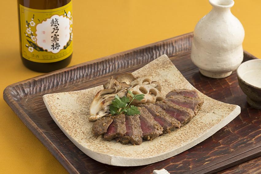 熟成肉のステーキと日本酒の写真