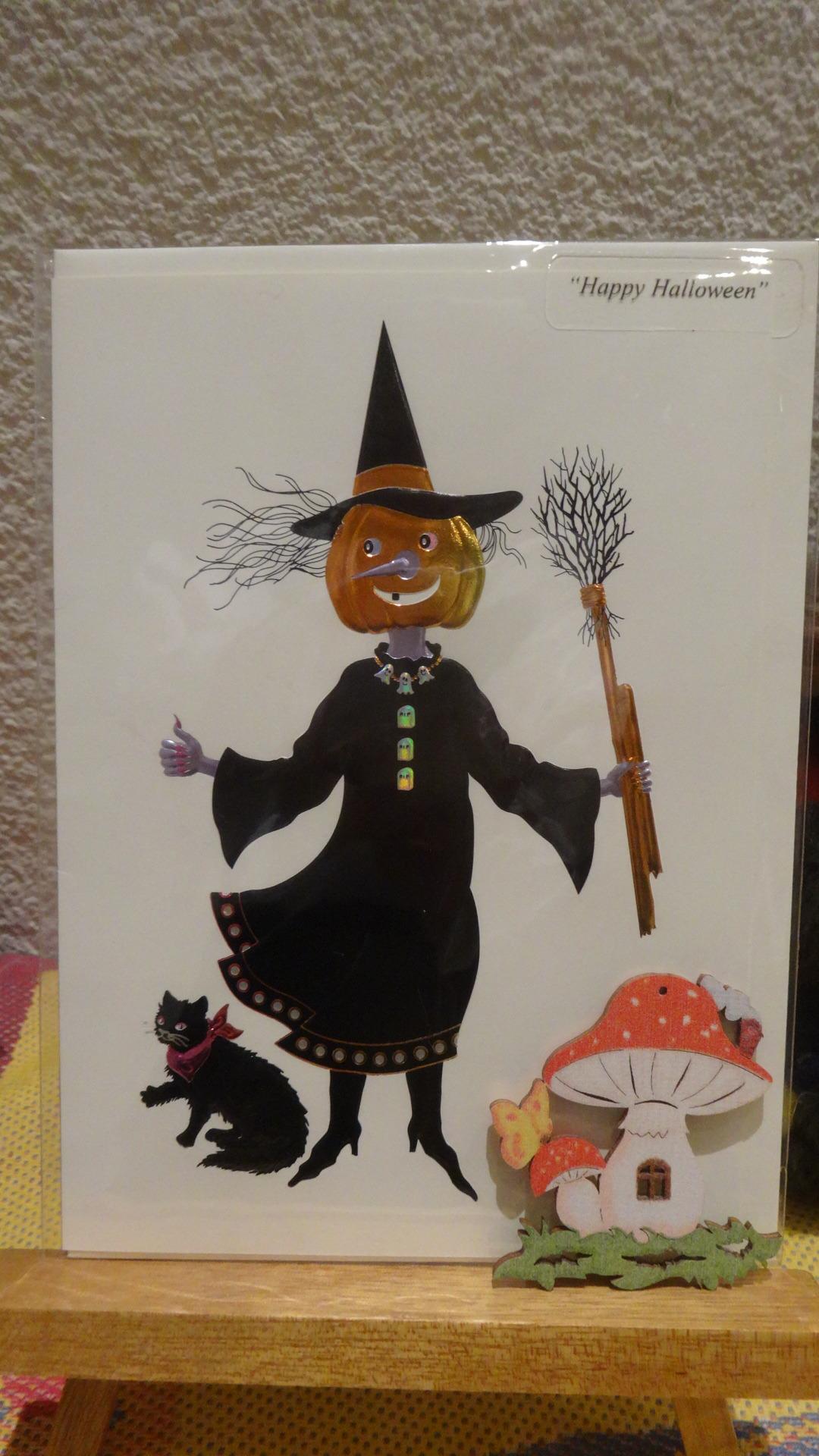 小さな魔女と黒ネコが描かれたカードが部屋に飾られている様子