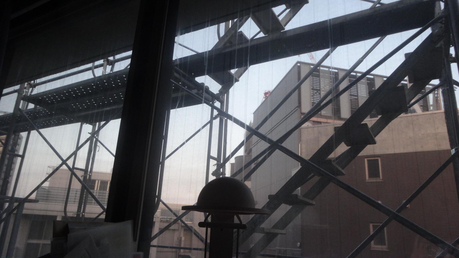 部屋のなかから見るビルの外壁に組まれた足場