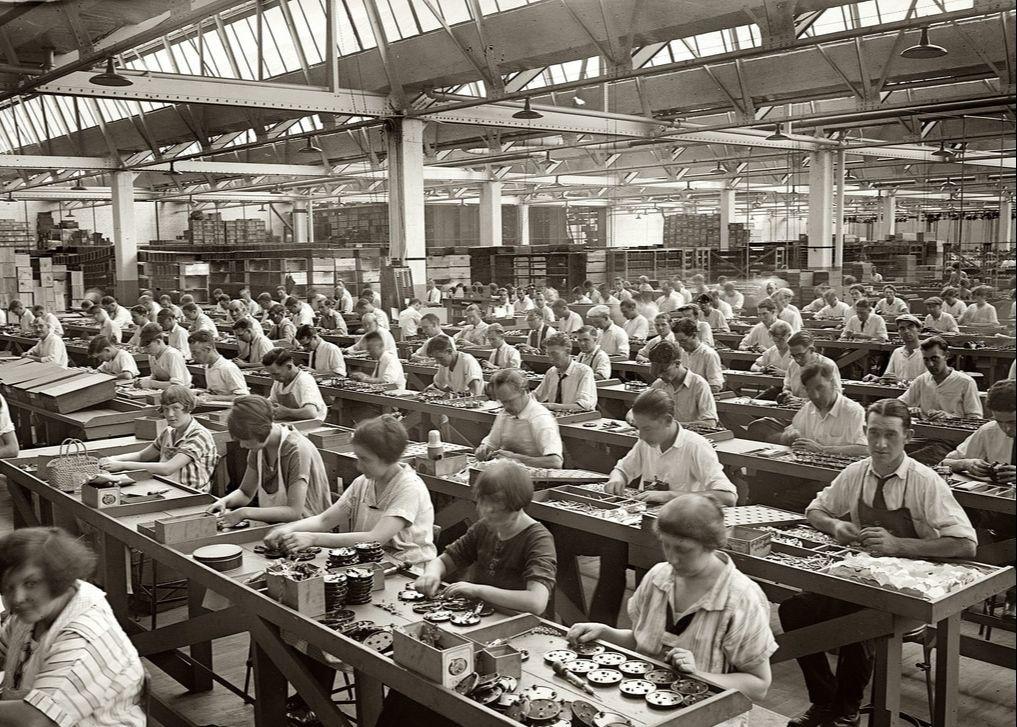 産業革命の時代に工場で座って作業する人たちの姿