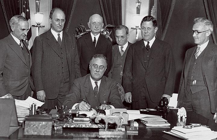 ニューディール政策にサインするルーズベルトの姿