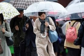 寒そうに傘をさす人