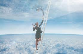 梯子に昇って頭上のガラスの天井を打ち破ろうとする女性のイメージ写真