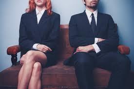 ひとつの椅子に隣同士で座る男女の写真