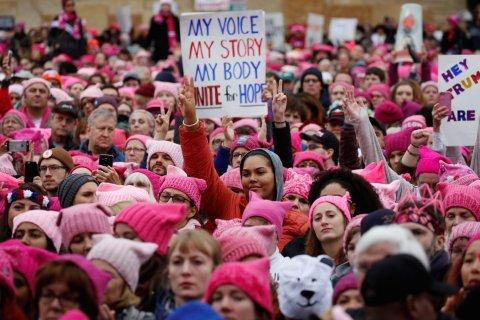 帽子を被ってデモ行進する人たち