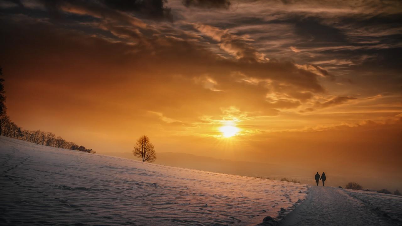 雪原に沈むロマンチックな夕日の光景