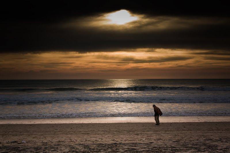 夕日が沈む海辺を一人歩く人の姿