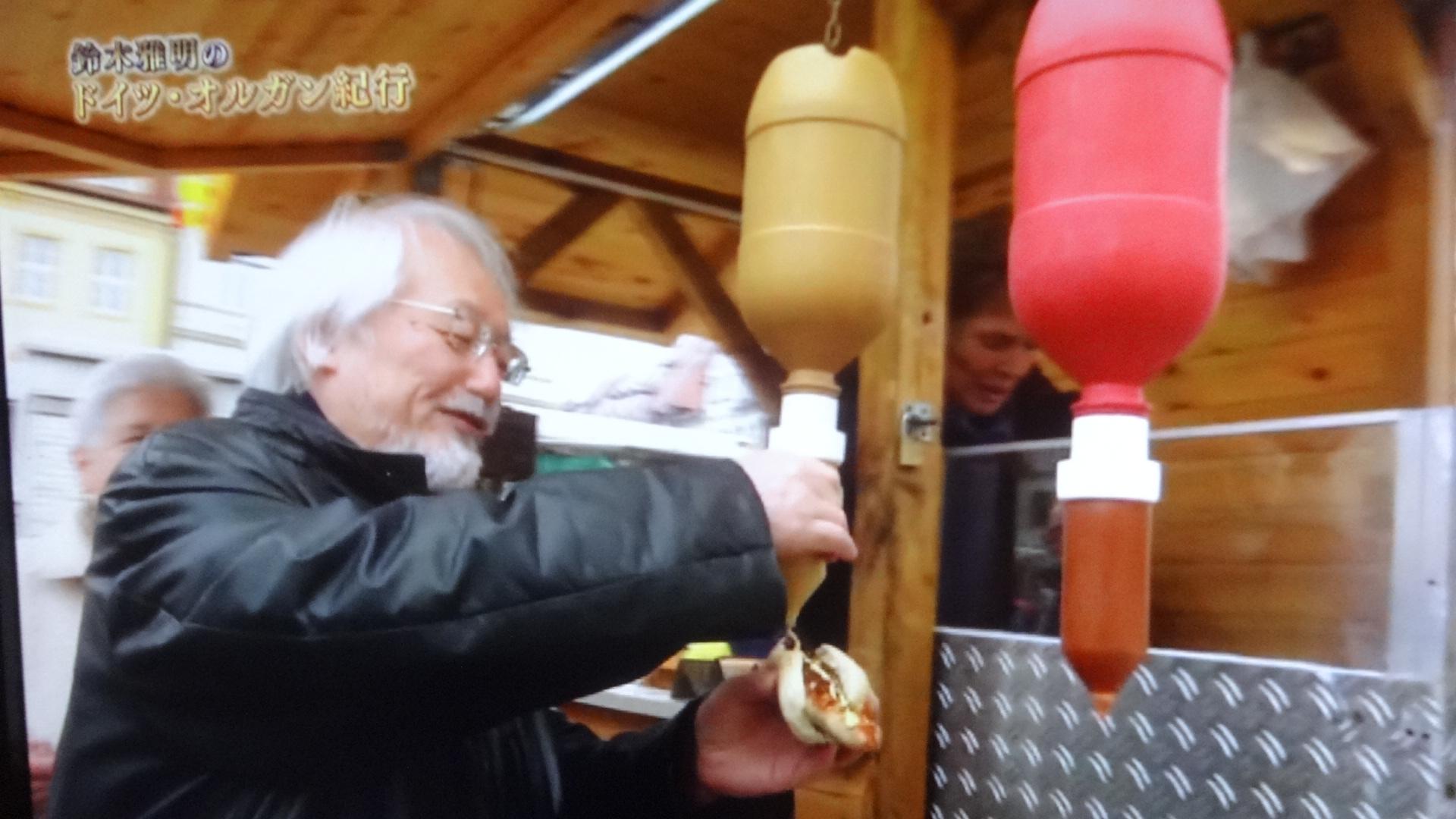 屋台でソーセージを食べる鈴木さん