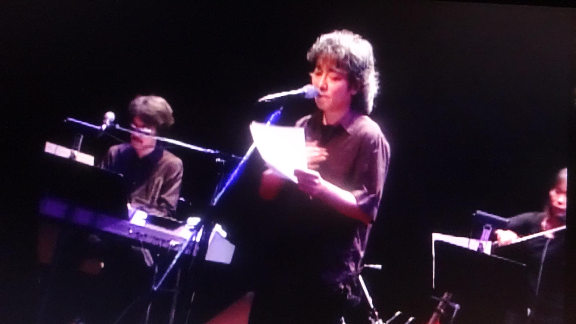 若い頃にステージで詩を朗読する佐野元春