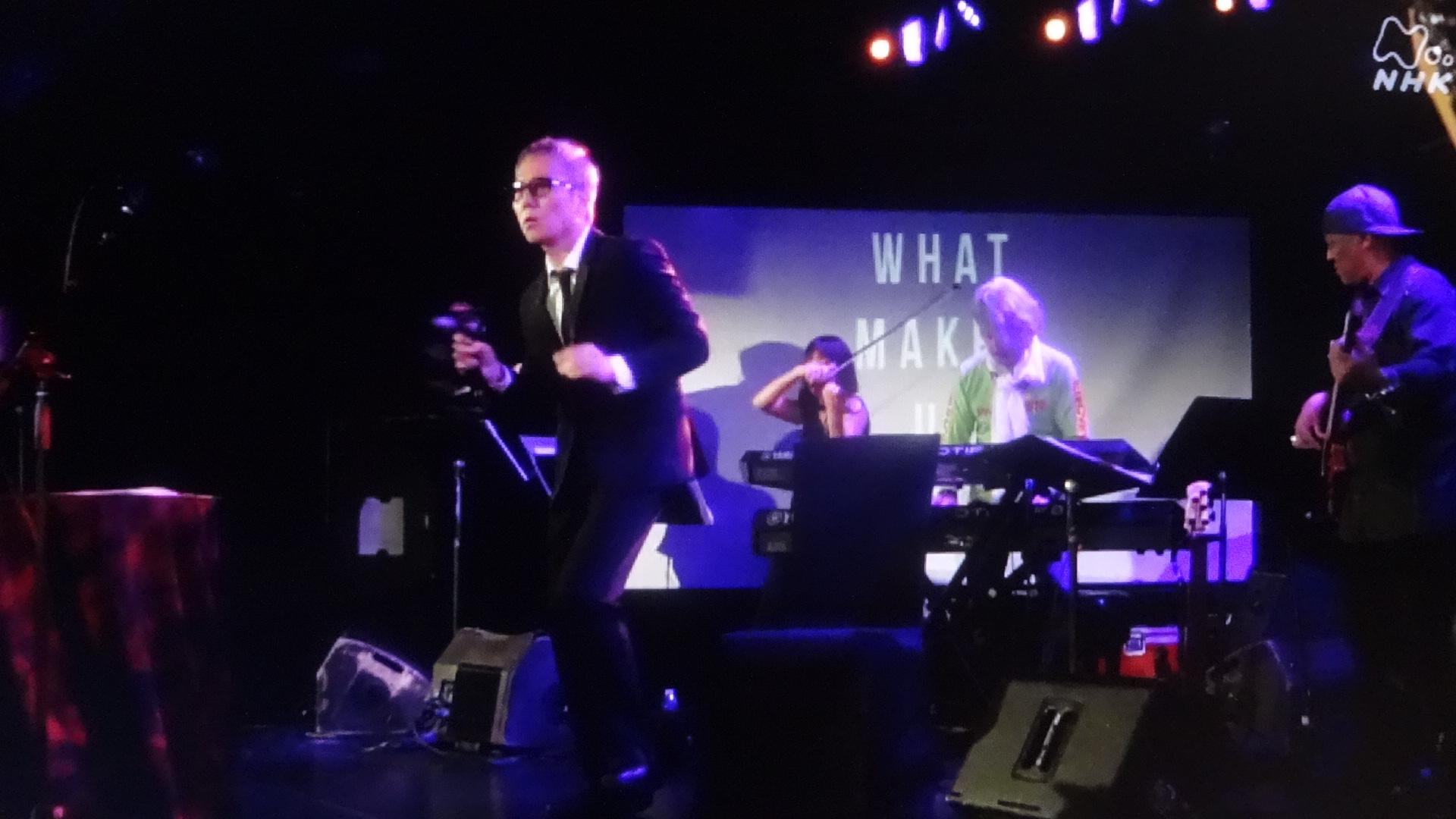 ニューヨークライブハウスのステージで詩を朗読する佐野元春2