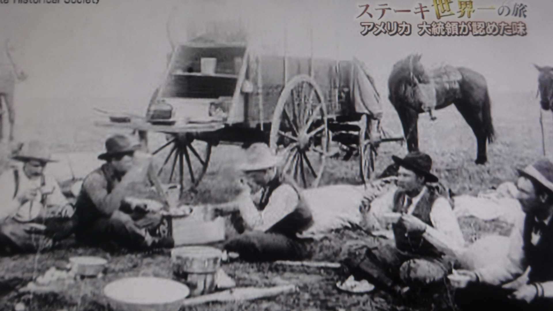 昔のカウボーイが屋外で食事している写真