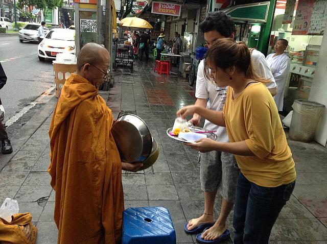 僧侶に食物を献上する人