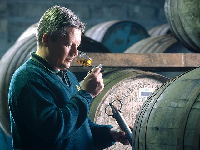 樽からウイスキーを採取して香りをかぐ人の姿