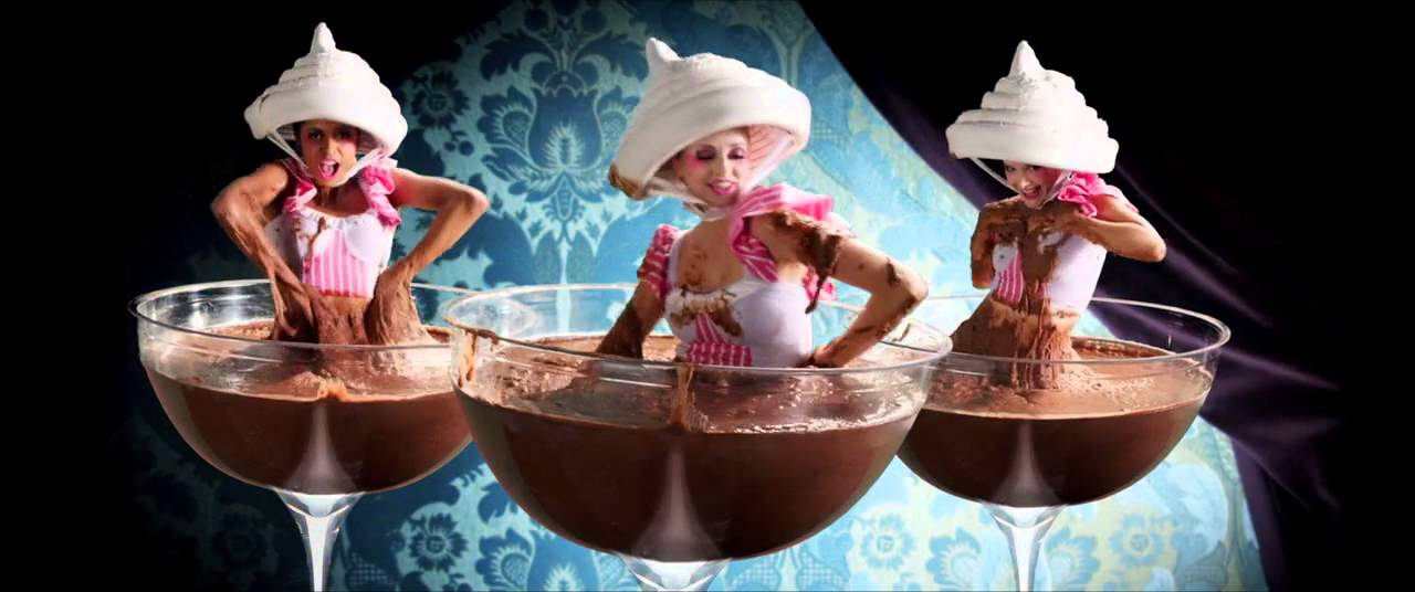 チョコレートのプールに全身浸って喜ぶ人々の写真