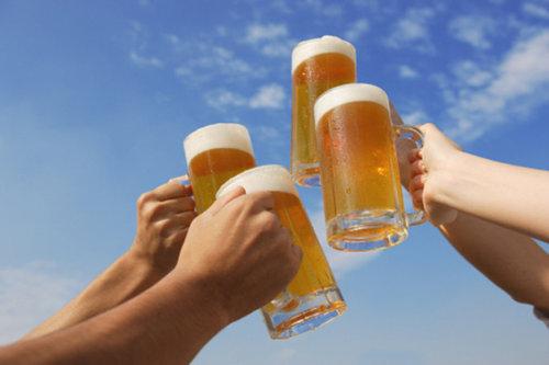 青空の下でビールで乾杯する人