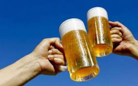 青空のもとでビールで乾杯する人の姿
