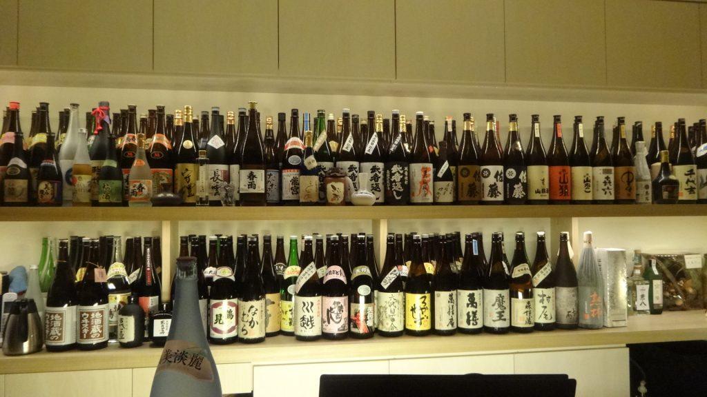 壁に並ぶたくさんの焼酎のボトル