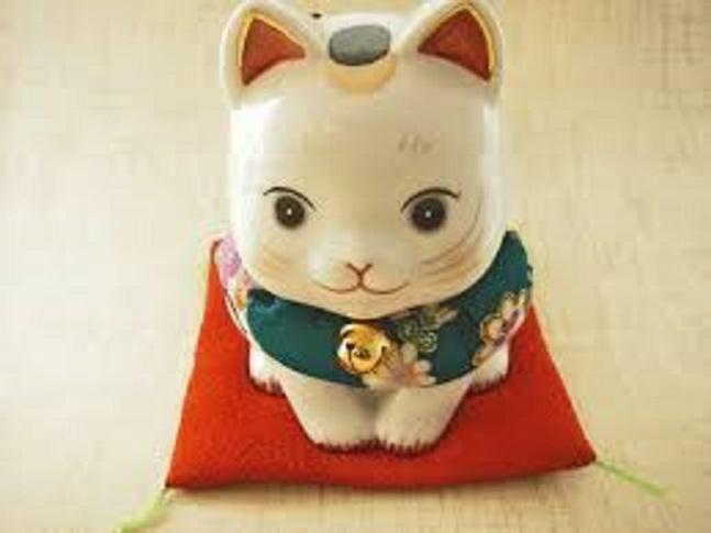 お礼するネコの人形