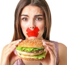 巨大なハンバーガーを頬張る人