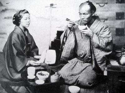 食器を手に持って食事をする江戸時代の人の写真