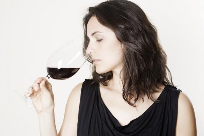 頭を前方に傾けてワインを飲む人