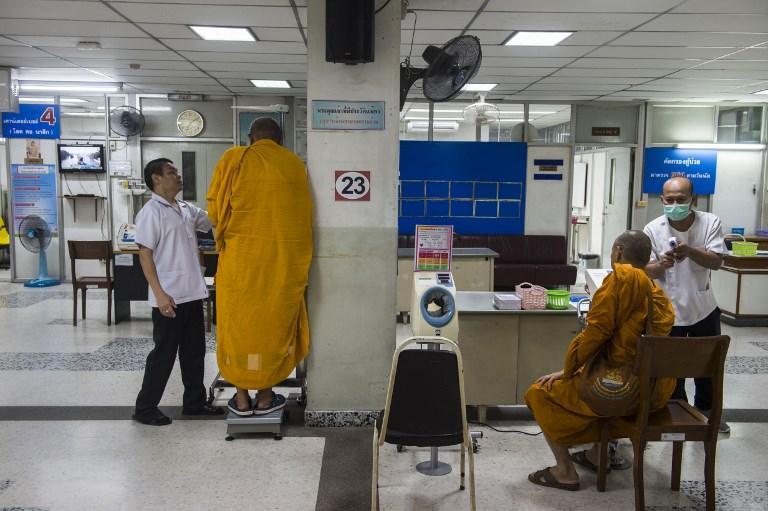 体重測定している僧侶