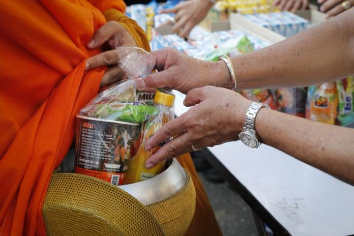 僧侶に栄養価の高い食物を托鉢する人