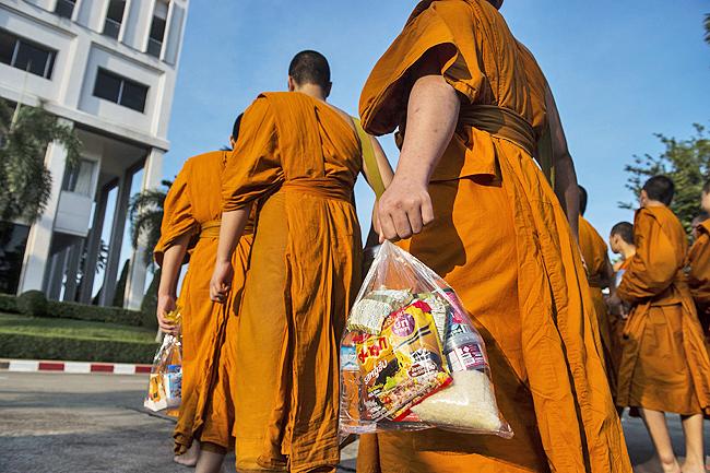 ジャンクフードの施しものを持つ僧侶