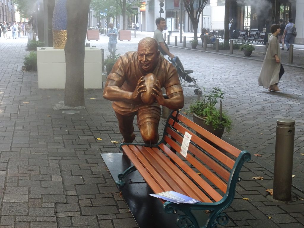 ベンチにトライしようとしているラガーマンの彫刻