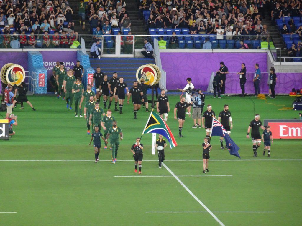 両国の国旗を先頭に入場する選手たち