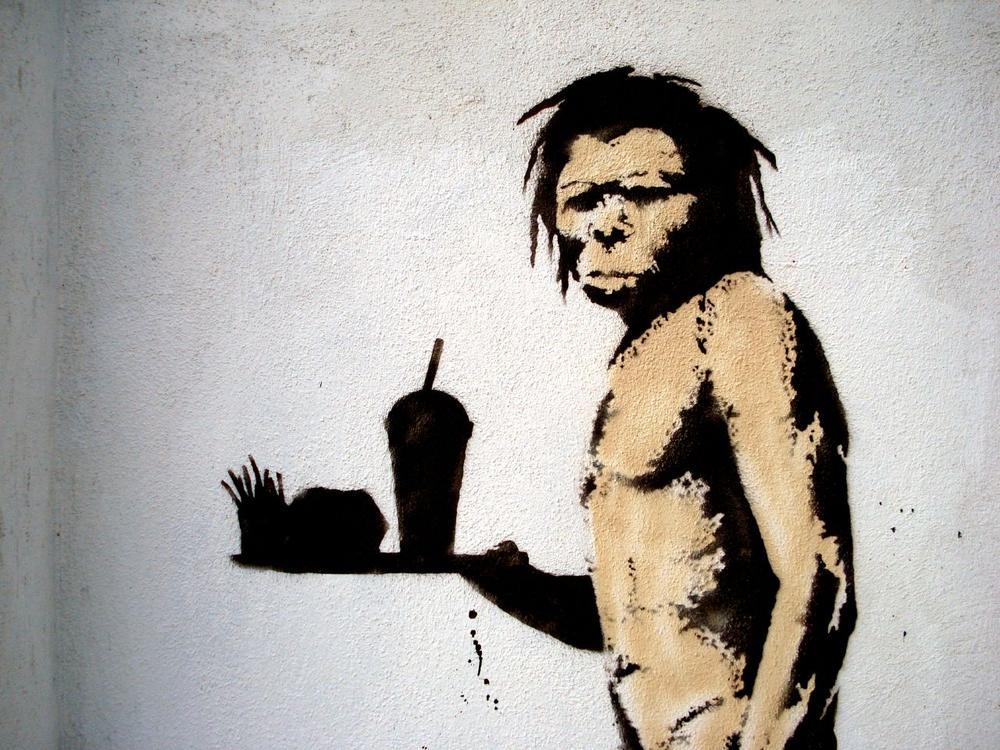 ファストフードを食べている人類の祖先のイラスト